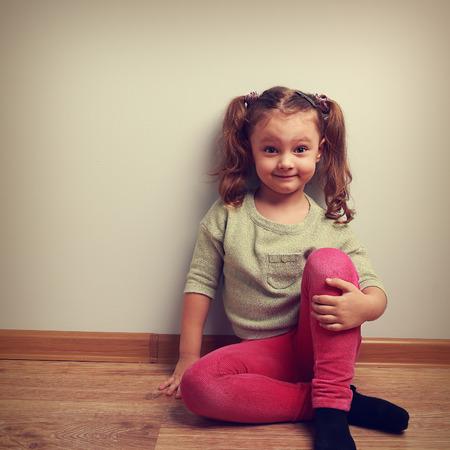 petite fille avec robe: Grimaçant fashion girl assis sur le plancher et souriant. Vintage closeup portrait