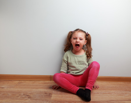 girl open mouth: Happy crying kid with open mouth sitting on the floor in fashion clothes Stock Photo