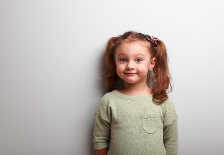 jovenes felices: Ni�a feliz divertido mirando con sonrisa en fondo azul de la pared