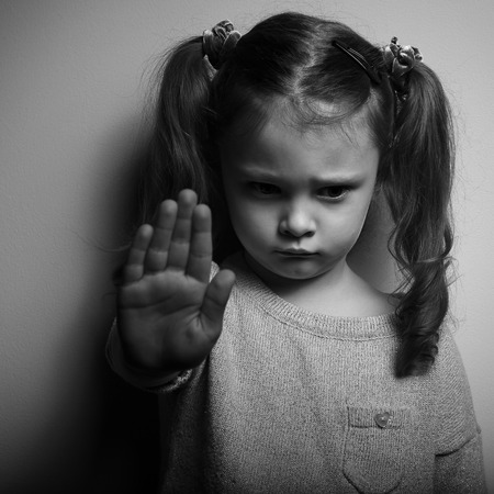 Kid girl showing hand signaling to stop violence and pain and looking down with sad face. Black and white portrait Stock Photo