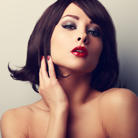 Hot sexy makeup model with short black hair style and red lipstick. Vintage closeup portrait photo