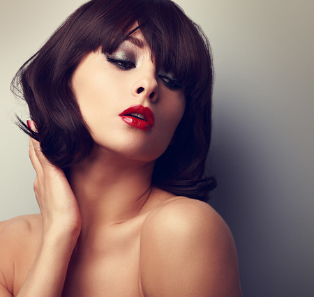Sexy model posing with black short hairstyle and red lipstick. Vintage closeup portrait photo