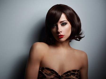 Sexual woman with black short hair looking on dark background with shadows photo