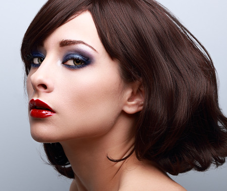 eyeshadow: Beautiful bright makeup with blue eyeshadows and red lipstick. Short hair style. Closeup
