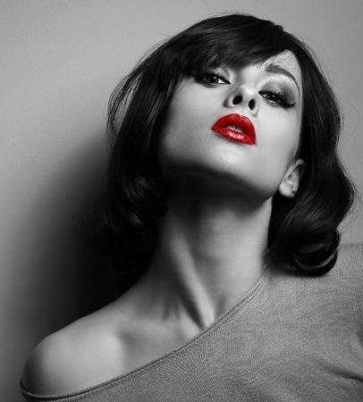 Sexy model met kort kapsel en rode lippen die zich voordeed op een donkere achtergrond. Zwart en wit