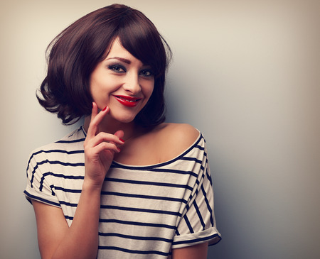 Thinking happy young woman with short hair looking on blue background with empty copy space. Vintage closeup color portrait