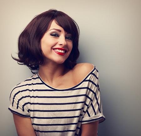 morena: Feliz mujer joven de risa con el pelo corto en la blusa de moda. Vintage retrato de cerca