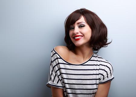 青いコピー スペース背景に髪の短い幸せ笑顔の若い女性