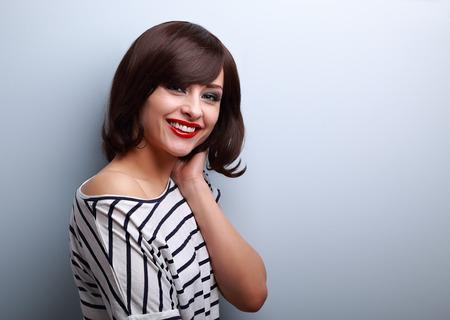 stile: Giovane e bella donna sorridente con breve capelli stile su sfondo blu