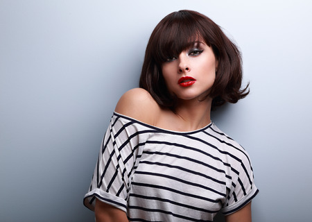Sexy makeup short hair woman in casual clothes posing on blue background with empty copy space photo
