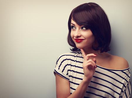 carita feliz: Mujer pensando feliz mirando con el dedo bajo la cara en el espacio vac�o de copia. Retrato del primer de la vendimia Foto de archivo