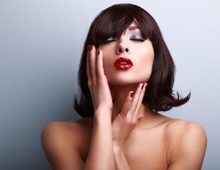 Beautiful makeup woman touching face. Red lipstick and manicured hands. Closeup portrait