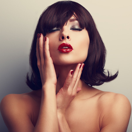 lips close up: Beautiful closed eyes woman touching face. Red lipstick and nails. Closeup portrait. Short hair style Stock Photo