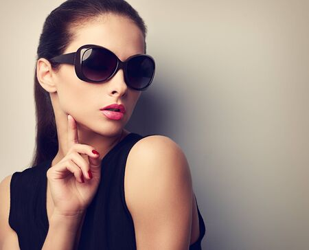 Elegant young female model in trendy sunglasses posing touching hand the face. Vintage closeup portrait with empty copy space photo
