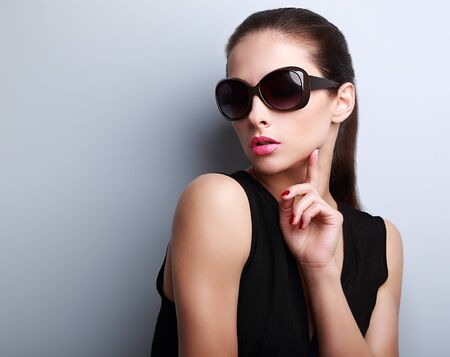 Sexy elegant beautiful female model in fashion sunglasses touching hand the face photo