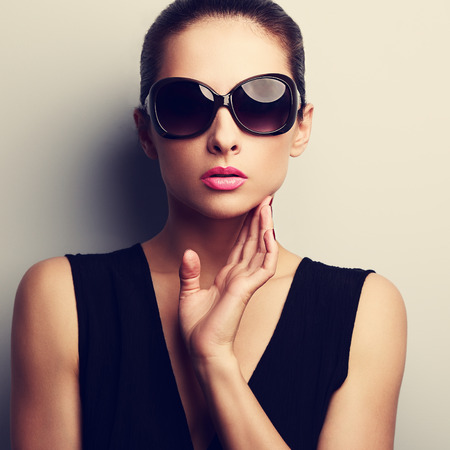 Sexy glamour female model in trendy sun glasses with hand at face. Closeup vintage portrait photo