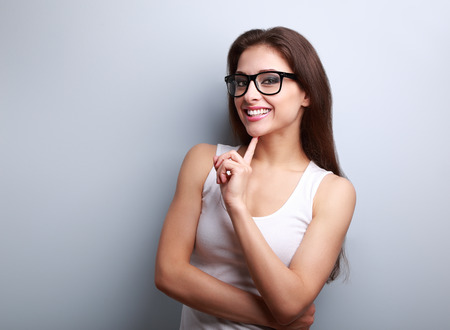 Happy toothy smiling young woman in glasses thinking on blue background with empty copy space