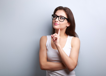 thinking woman: Thinking young woman in glasses looking on empty space background