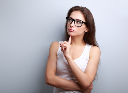 distrust: Beautiful serious thinking young woman looking up on empty copy space Stock Photo