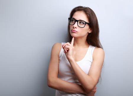 desconfianza: Hermoso pensamiento serio mujer joven que mira para arriba en el espacio vacío de la copia