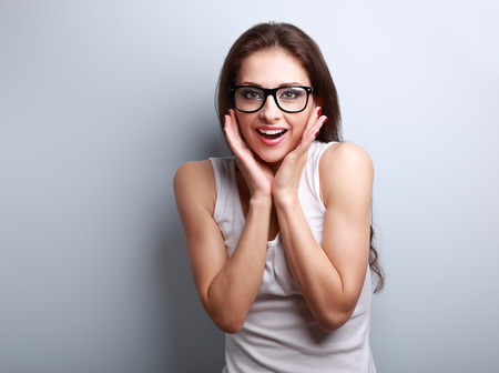 excited woman: Excited surprising fun young woman with open mouth in glasses on blue background with empty copy space