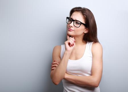 desconfianza: Pensando en la mujer joven serio en vidrios mira en vacío fondo espacio de la copia