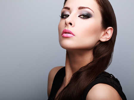 long hair brunette: Sexy perfect makeup woman looking with smoky eyes and pink lips on blue background. Closeup portrait Stock Photo