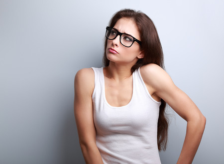 enojo: La ira joven casual en gafas pensando y mirando hacia arriba sobre fondo azul con el espacio vacío de la copia