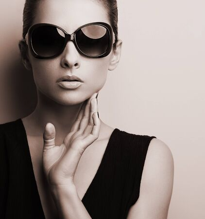 Stylish fashion female model in fashion sunglasses posing. Black and white color toned portrait photo