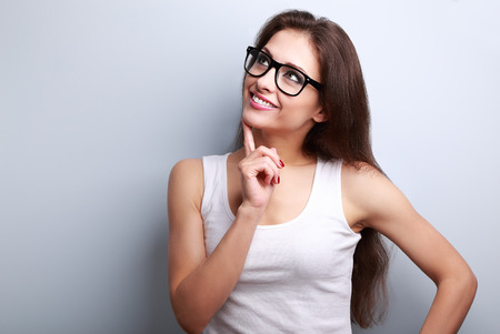 woman think: Healthy young thinking woman in glasses looking up on blue background with empty copy space