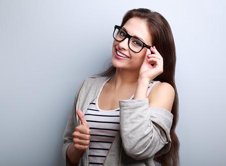 엄지 손가락을 파란색 배경에 빈 복사본 공간에 게재하는 안경에 행복 하 게 웃 고 젊은 여자 스톡 콘텐츠