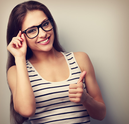 Smiling beautiful casual woman in fashion glasses showing thumb up. Closeup vintage portrait Stock Photo
