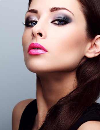 the lipstick: Beautiful woman with bright smokey makeup eyes and pink lipstick. Perfect closeup make-up and foundation Stock Photo