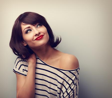 hair short: Pensamiento feliz corta el pelo maquillaje mujer y mirando hacia arriba en la blusa moderna. Vintage retrato de cerca