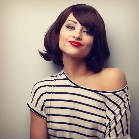 Pretty young woman grimacing with short black hair style in fashion blouse. Vintage closeup portrait