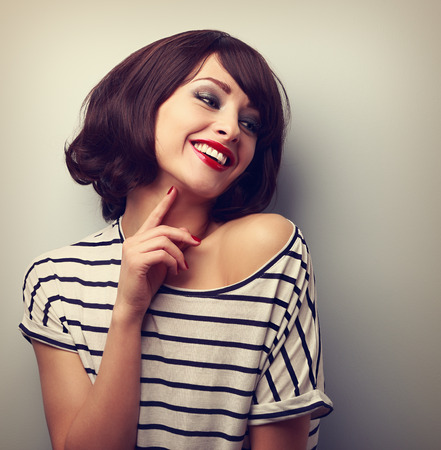 woman hairstyle: Happy laughing young short hairstyle woman in fashion blouse touching neck. Vintage closeup portrait