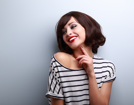 Happy natural laughing young short hairstyle woman in fashion blouse on blue background