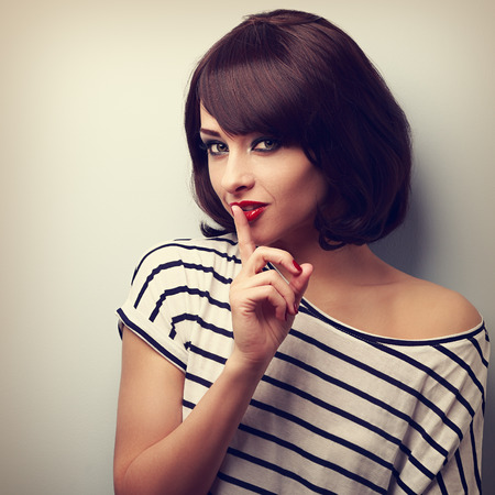 Beautiful makeup young woman showing silence sign. Short hair style. Vintage closeup portrait