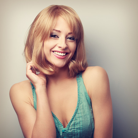 Happy laughing short hair blond woman. Bright makeup. Closeup toned portrait