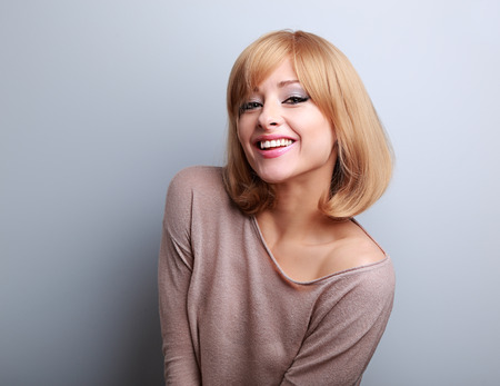 Happy young blonde woman in fashion blouse laughing on blue background