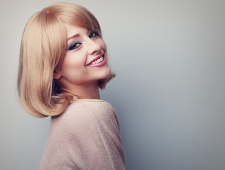 Beautiful tooth smiling woman with short blond hair looking happy. Color toned closeup portrait with empty copy space Archivio Fotografico
