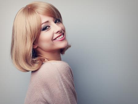 cabello rubio: Hermosa mujer sonriente del diente con el pelo corto y rubio que parece feliz. En tonos de color retrato de cerca con el espacio vac�o de la copia Foto de archivo