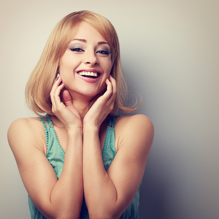 blonde girls: Happy laughing blond young woman holding hand at face. Toned closeup portrait