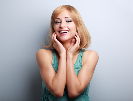 blue face: Happy laughing blond young woman holding hand at face on blue background with empty copy space