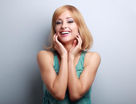 rubia: Risa feliz mujer rubia joven con la mano en la cara en el fondo azul con el espacio vacío de la copia