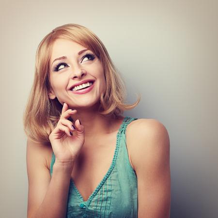 mujer pensando: Feliz dentudo sonrisa pensamiento mujer rubia y mirando hacia arriba. Retrato de tonos con el espacio vacío