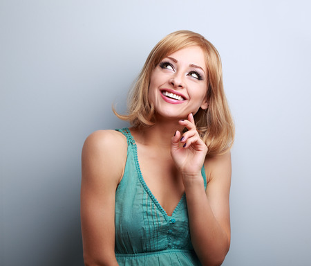 thinking woman: Happy toothy smiling blond woman thinking and looking up on blue empty space background