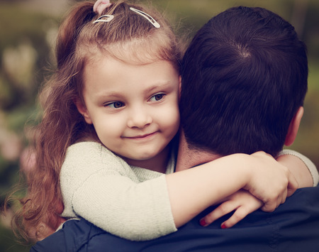 Happy pretty smiling kid girl hugging her father with love outdoor. Toned closeup color portrait photo