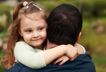Happy pretty smiling kid girl hugging her father with love outdoor summer background photo