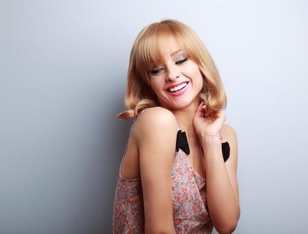rubia: Relájese riendo joven rubia con estilo de pelo corto mirando hacia abajo